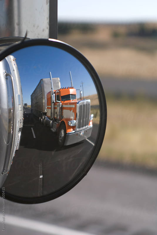 A passing truck in another truck's side mirror by Tana Teel for Stocksy United