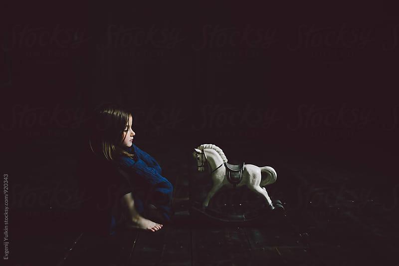 Child sitting next to toy hourse by Evgenij Yulkin for Stocksy United