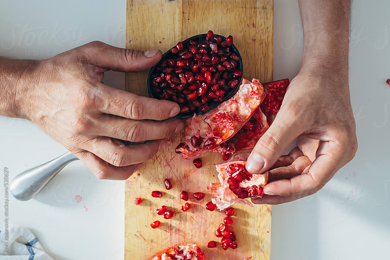 Man's hands peeling fresh pomegranate  by Jovo Jovanovic for Stocksy United