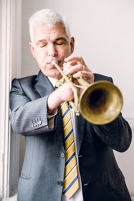 silver haired man with eyes closed blowing into trumpet by Lisa MacIntosh for Stocksy United