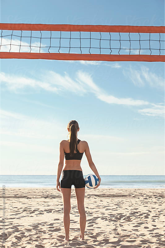Beach volleyball. Sporty woman looking at sea with a ball. by BONNINSTUDIO for Stocksy United