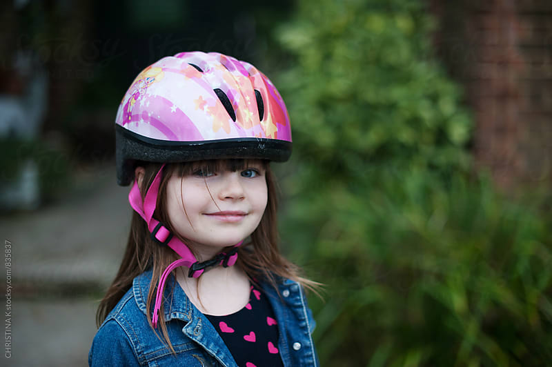 Smiling girl wearing a bike safety helmet by CHRISTINA K for Stocksy United