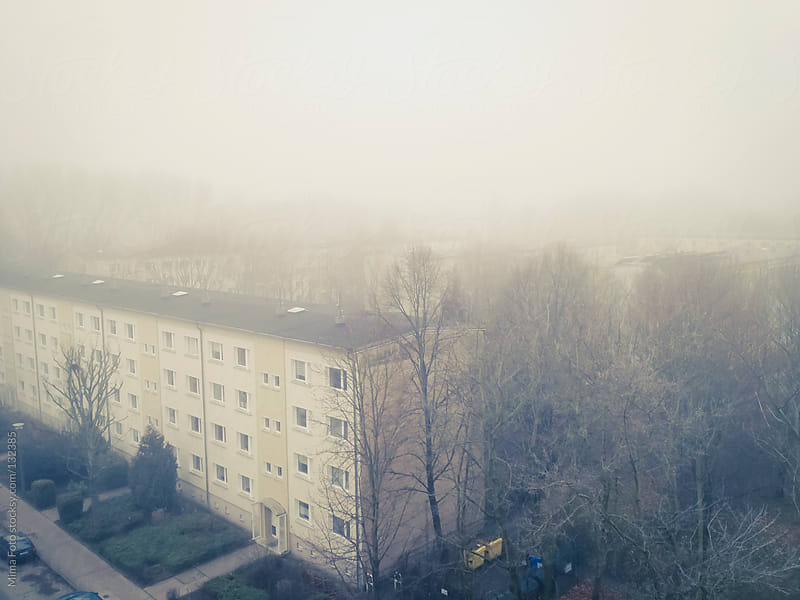 Heavy fog over post-war residential area by Mima Foto for Stocksy United