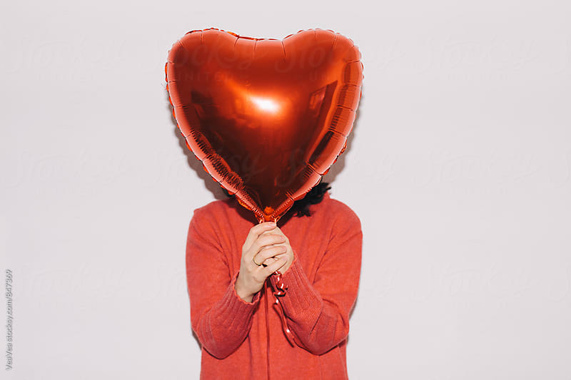 Woman holding a red Valentine's ballon  by VeaVea for Stocksy United