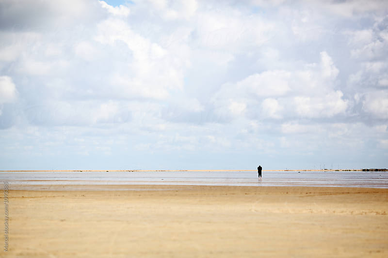 Silhouetted man on an endless beach by Marcel for Stocksy United