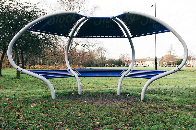 Covered public seating in parkland by Paul Phillips for Stocksy United