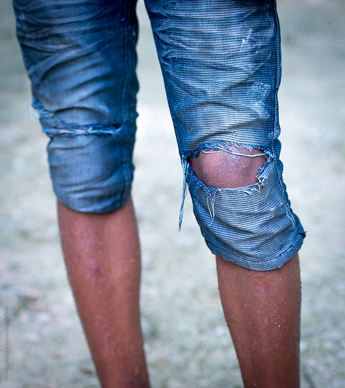 Close-up of cliff diver's legs in torn blue jeans by Trent Lanz for Stocksy United