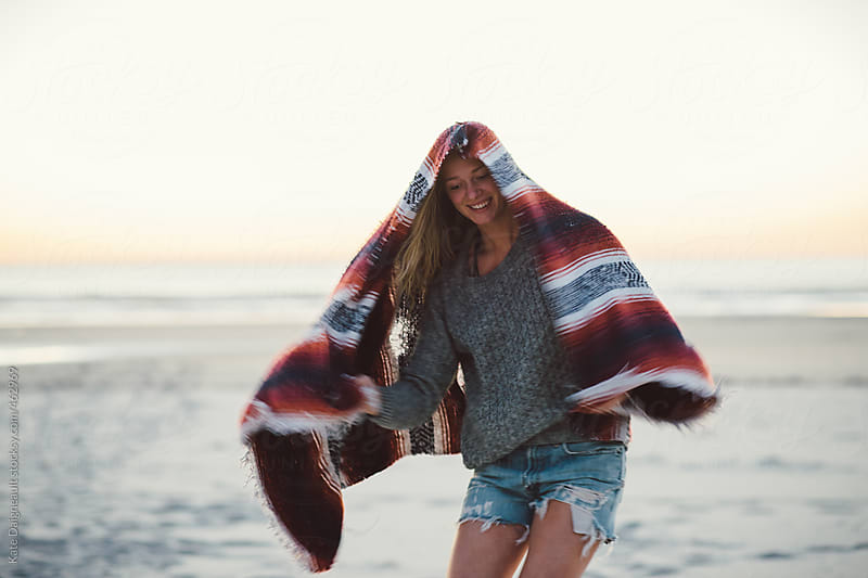 Beautiful young woman on the beach at sunset by Kate Daigneault for Stocksy United