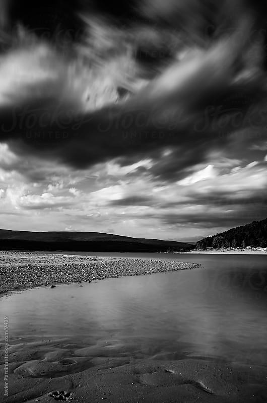 Landscape with black and white with a calm lake in Soria, Spain with incoming storm on sky.  by Javier Pardina for Stocksy United