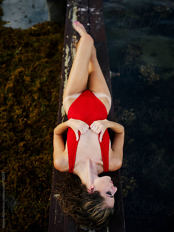 Lady In Red Lying On Pier by Marlon Richardson for Stocksy United