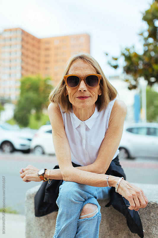 Portrait of a senior woman sitting on the street. by BONNINSTUDIO for Stocksy United