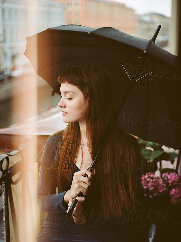 Young woman with a black umbrella by Liubov Burakova for Stocksy United