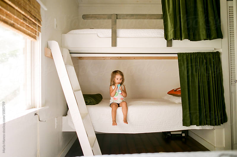little girl on bunk bed by Maria Manco for Stocksy United