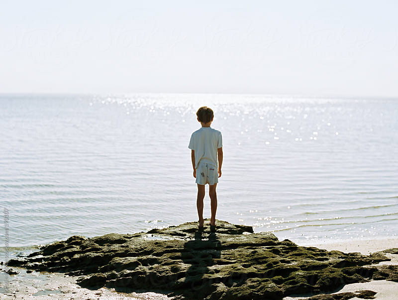 Boy standing on rocks and looking out towards the sea by Kirstin Mckee for Stocksy United