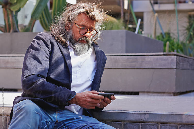 Really cool old guy using technology by Aila Images for Stocksy United
