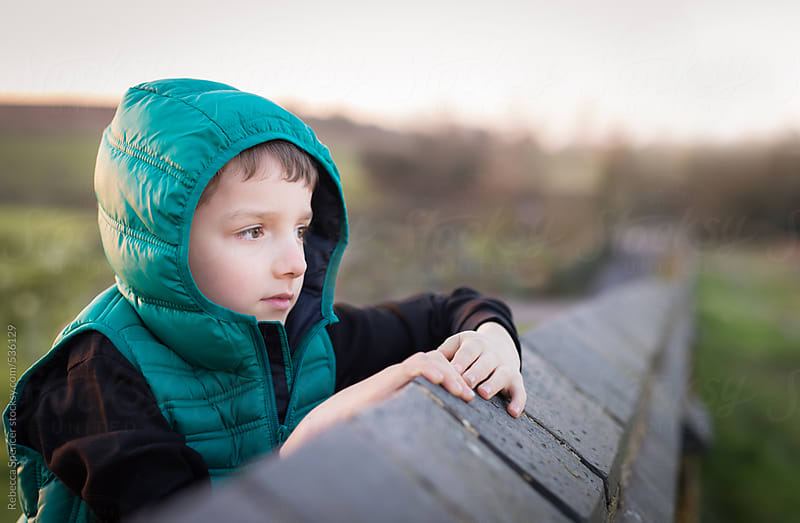 Child looking intently over a wall by Rebecca Spencer for Stocksy United