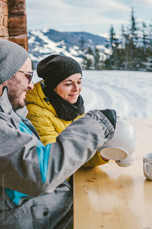 young couple drinking tea outdoors in alpine winter landscape by Leander Nardin for Stocksy United