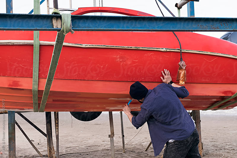 Back view of carpenter restorating red boat by Danil Nevsky for Stocksy United