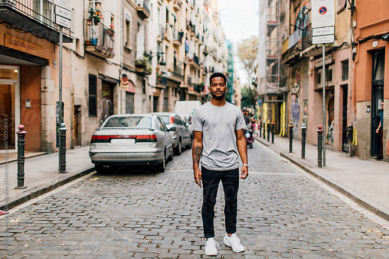 A man standing in the middle of the street in Barcelona, Spain by Kristen Curette Hines for Stocksy United