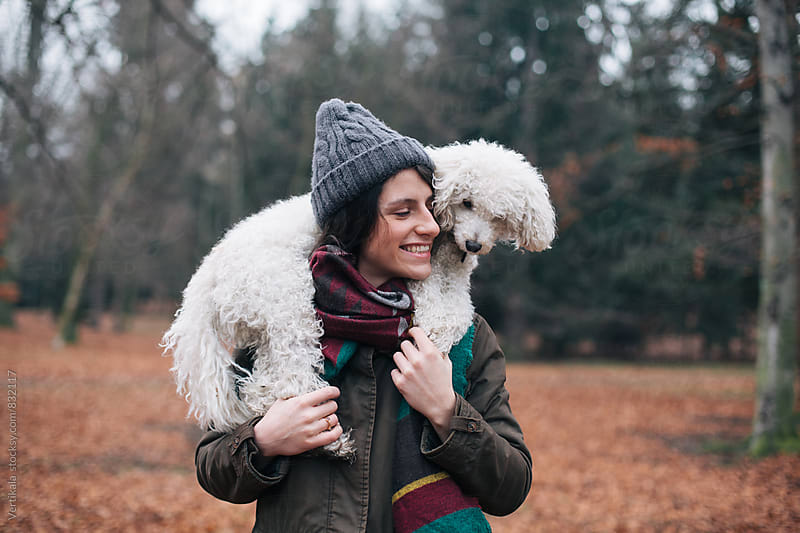 Beautiful happy woman having fun with her dog in nature  by VeaVea for Stocksy United