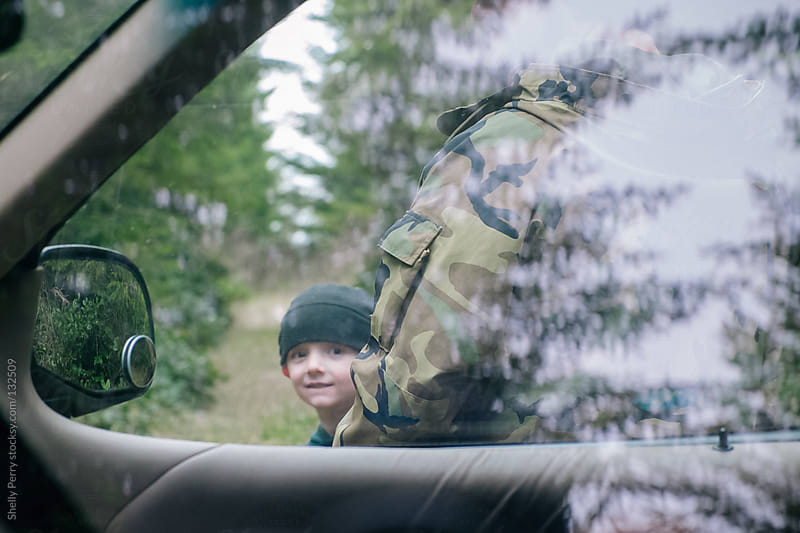 Boy in nature looking through car window by Shelly Perry for Stocksy United