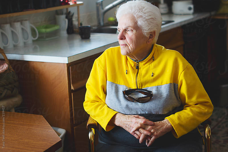An older woman looks out her kitchen window by Tana Teel for Stocksy United