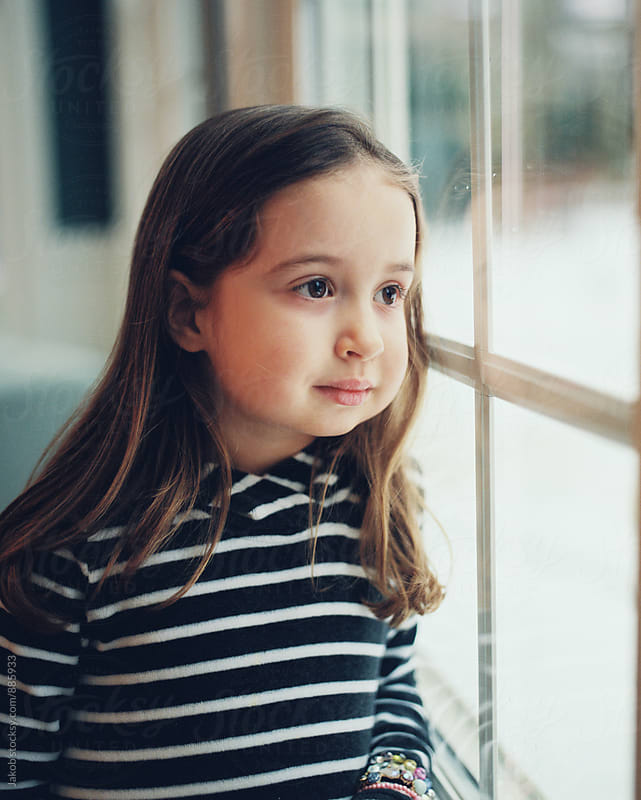 Beautiful young girl looking out a window by Jakob for Stocksy United