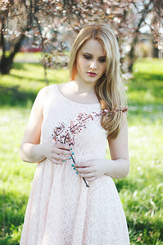 Young woman holding cherry blossom twig  by Jovana Rikalo for Stocksy United