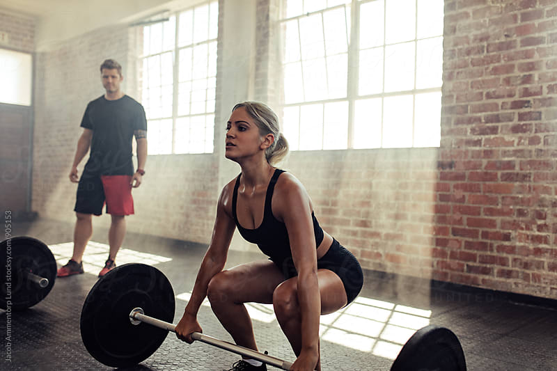 Young woman doing squats in gym with barbell by Jacob Ammentorp Lund for Stocksy United