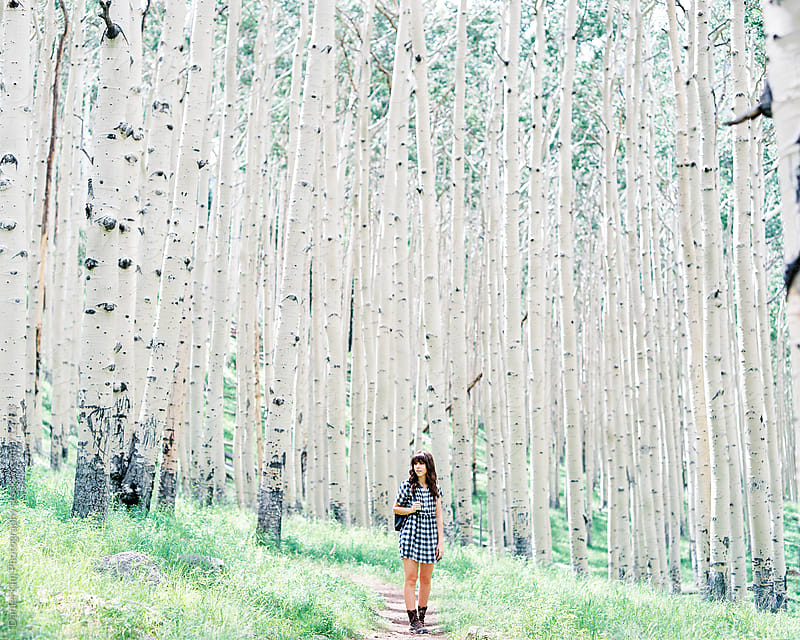 Woman walking in white tree forest by Daniel Kim Photography for Stocksy United