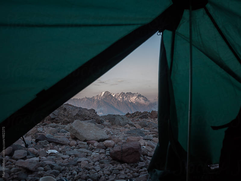 VIew at the snowy mountains from tent by Martin Matej for Stocksy United