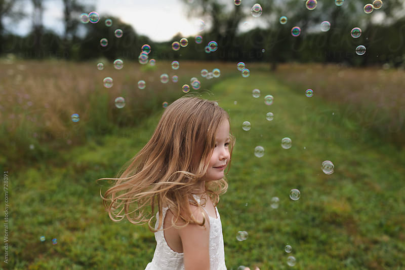 Young girl twirls in a field with bubbles all around her by Amanda Worrall for Stocksy United