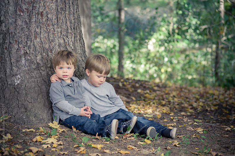 Young brothers sitting in the woods by Jen Grantham for Stocksy United