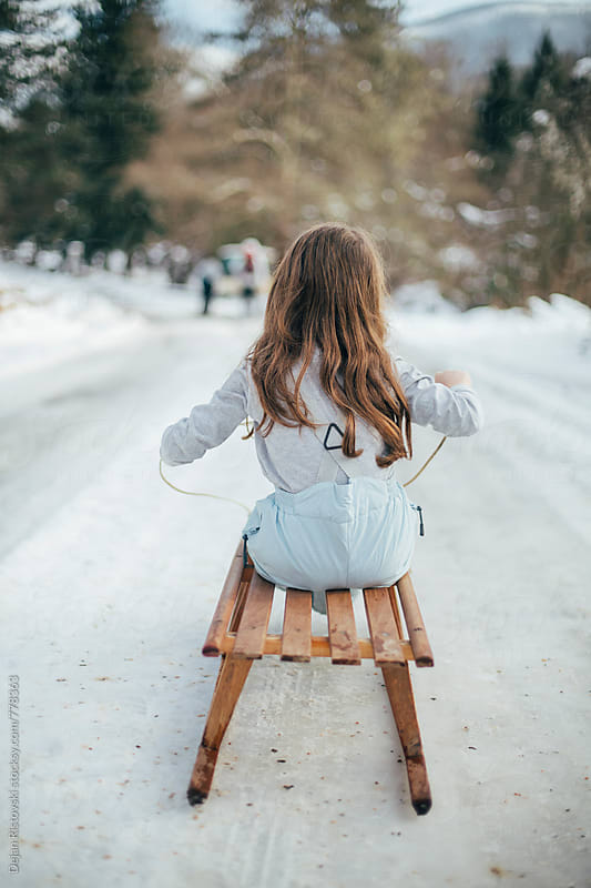 Girl sitting on a sledge. by Dejan Ristovski for Stocksy United
