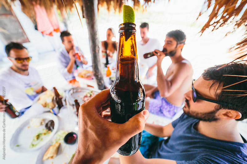 Young man hand holding a refreshing beer bottle with group of friends drinking in the background at a beach bar by Alejandro Moreno de Carlos for Stocksy United