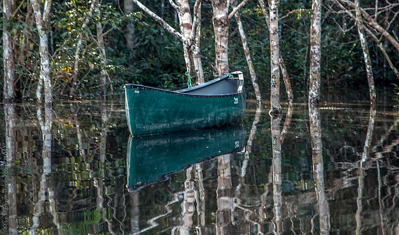 A canoe on a river moored by trees. by Mike Marlowe for Stocksy United