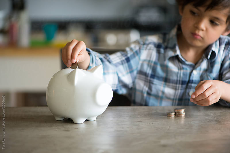 young child inserts a coin into his piggy bank by Tara Romasanta for Stocksy United