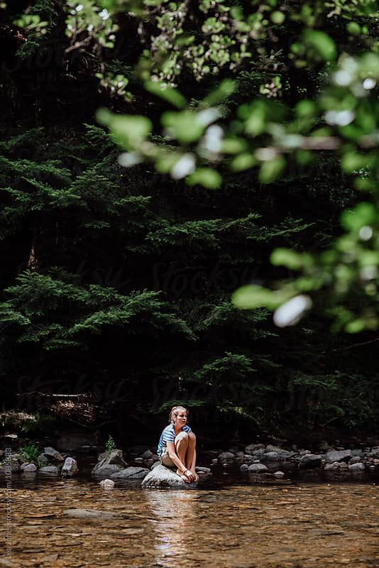 teen on rock in the river by Léa Jones for Stocksy United