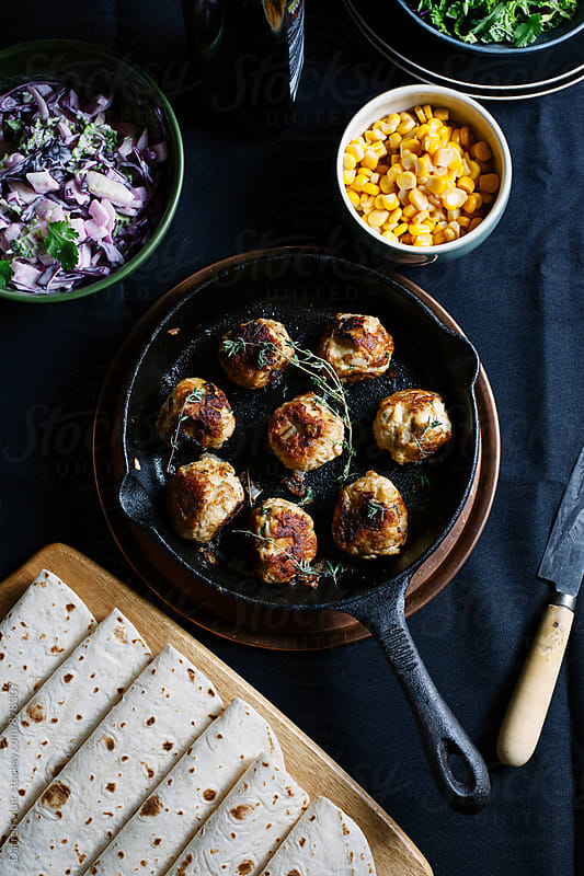 Meatball meal on a dark table cloth. by Darren Muir for Stocksy United