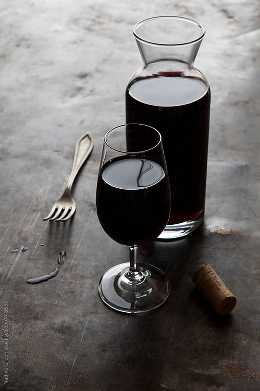 Wine carafe with glass of red wine, spills, fork and a cork by Nadine Greeff for Stocksy United