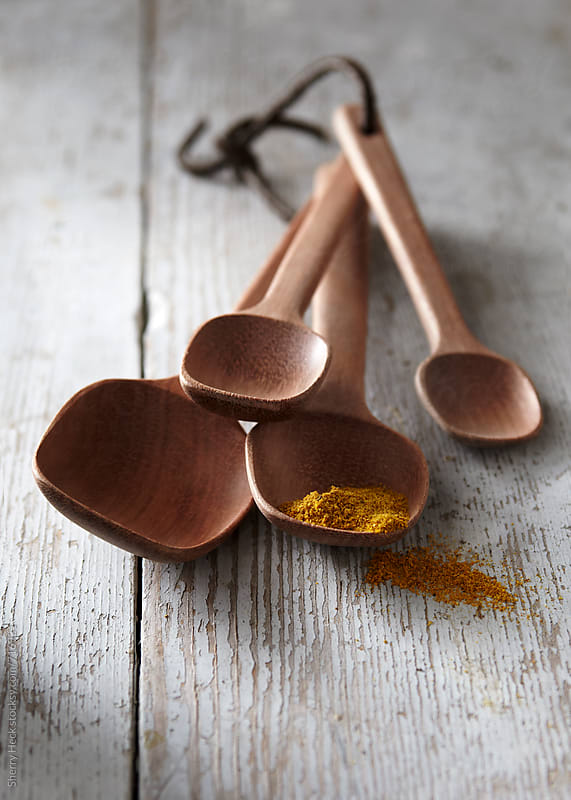 Wood measuring spoons with spice spilling onto whitewashed wood surface by Sherry Heck for Stocksy United
