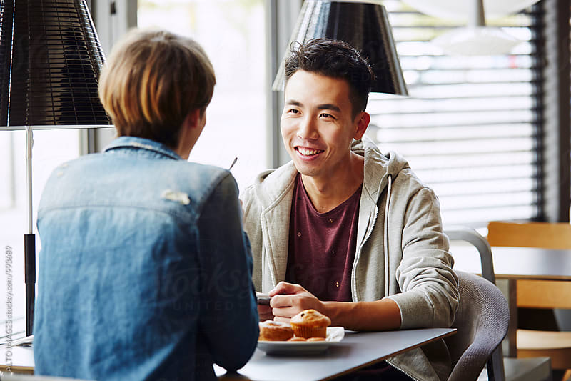 Happy Man Talking With Woman In Cafe by ALTO IMAGES for Stocksy United