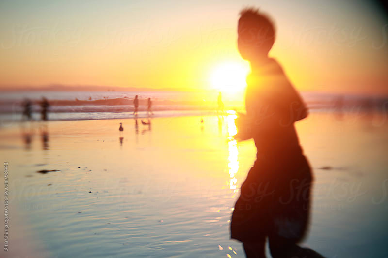 Silhouette of boy running across beach at sunset with orange and yellow sky by Dina Giangregorio for Stocksy United