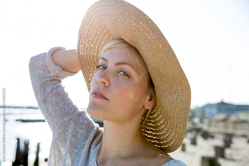 Woman on the beach wearing her hat by Ann-Sophie Fjelloe-Jensen for Stocksy United