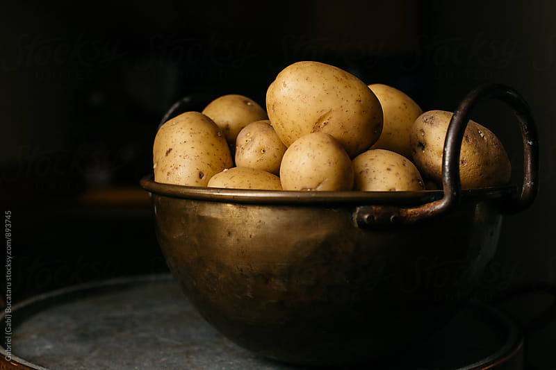 Brass bowl with yellow potatoes by Gabriel (Gabi) Bucataru for Stocksy United
