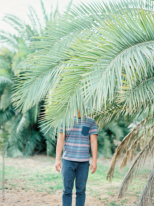 Male standing behind tree by Daniel Kim Photography for Stocksy United
