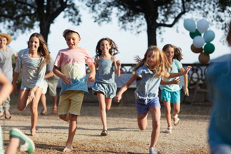 Group of children running at an outdoors party by Miquel Llonch for Stocksy United