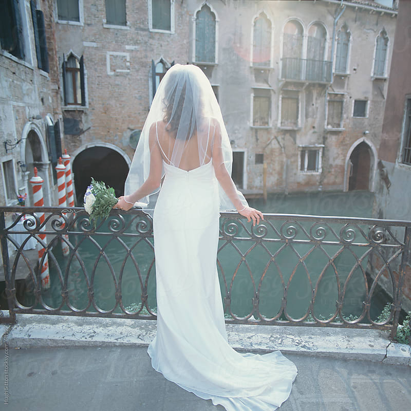 Bride in wedding dress on bridge overlooking canal. Venice. Italy. by Hugh Sitton for Stocksy United