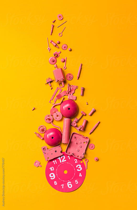 Disassembled pink clock on orange background. by Marko Milanovic for Stocksy United