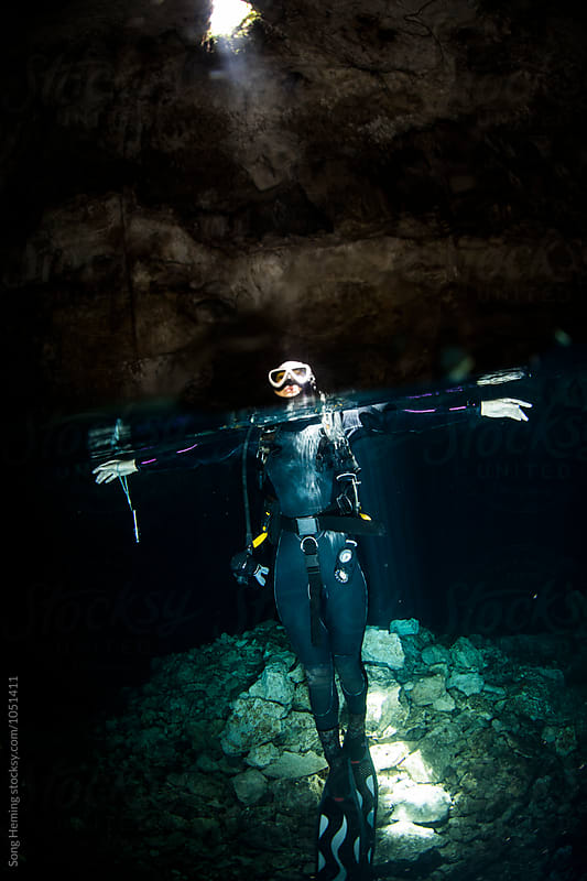 A scuba diver floating on surface in Mexico's Tajma ha Cenote by Song Heming for Stocksy United
